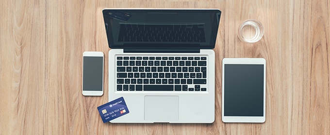 Laptop, telefoon, tablet en creditcard op tafel